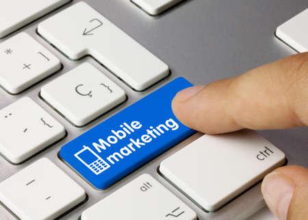 Mobile marketing Written on Blue Key of Metallic Keyboard. Finger pressing key.