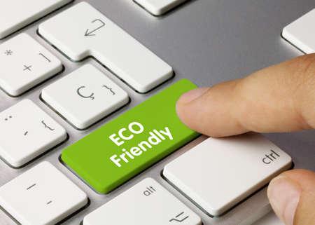 ECO Friendly Written on Green Key of Metallic Keyboard. Finger pressing key.