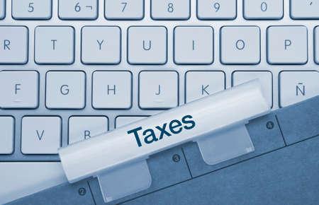 Taxes Written on Blue Key of Metallic Keyboard. Finger pressing key.