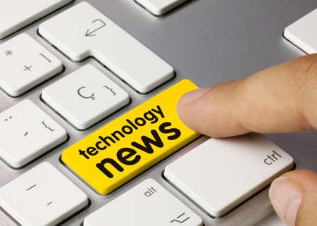 Technology news Written on Yellow Key of Metallic Keyboard. Finger pressing key. Banco de Imagens