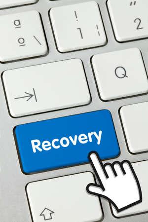 Recovery Written on Blue Key of Metallic Keyboard. Finger pressing key.