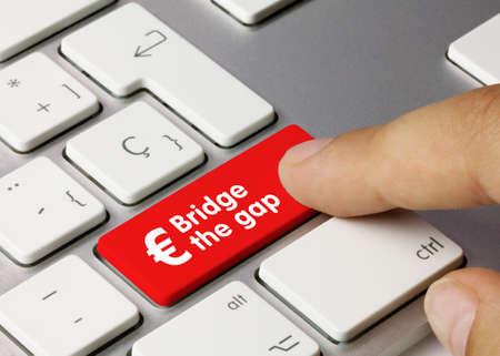 Bridge the gap euro Written on Red Key of Metallic Keyboard. Finger pressing key.