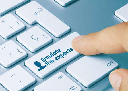Emulate the experts Written on Blue Key of Metallic Keyboard. Finger pressing key. 版權商用圖片
