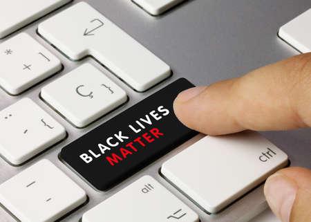 Black Lives Matter Written on Black Key of Metallic Keyboard. Finger pressing key.