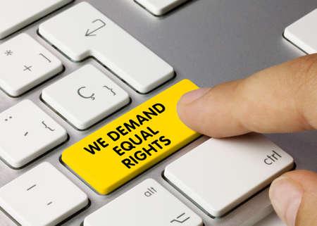 WE DEMAND EQUAL RIGHTS Written on Yellow Key of Metallic Keyboard. Finger pressing key. Zdjęcie Seryjne