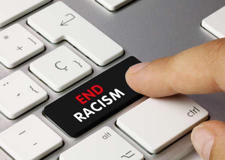 End Racism Written on Black Key of Metallic Keyboard. Finger pressing key.