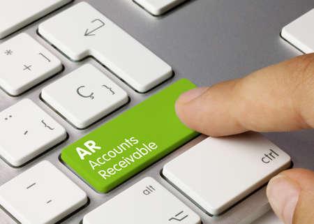AR Accounts Receivable Written on Green Key of Metallic Keyboard. Finger pressing key.