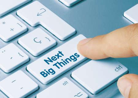 Next Big Things Written on Blue Key of Metallic Keyboard. Finger pressing key.