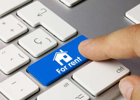 Home for rent Written on Blue Key of Metallic Keyboard. Finger pressing key. Stock fotó