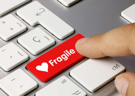 Fragile Written on Red Key of Metallic Keyboard. Finger pressing key.
