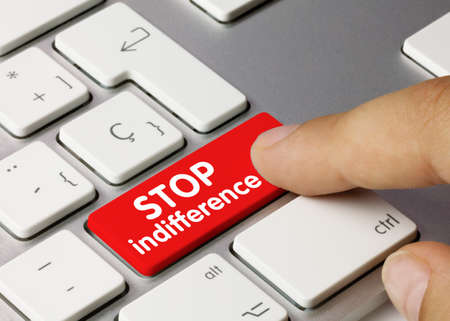 Stop indifference Written on Red Key of Metallic Keyboard. Finger pressing key.