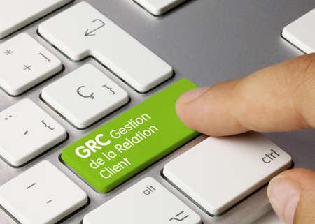 GRC Gestion de la Relation Client Written on Green Key of Metallic Keyboard. Finger pressing key.