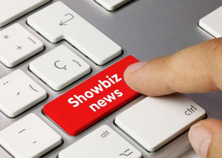 Showbiz news Written on Red Key of Metallic Keyboard. Finger pressing key.