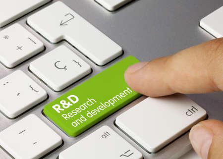 R&D Research and Development Written on Green Key of Metallic Keyboard. Finger pressing key.