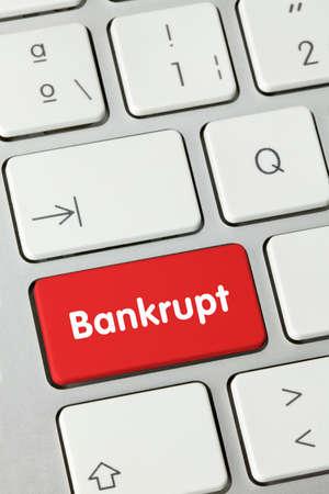 Bankrupt Written on Red Key of Metallic Keyboard. Finger pressing key.