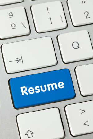 Resume Written on Blue Key of Metallic Keyboard. Finger pressing key.