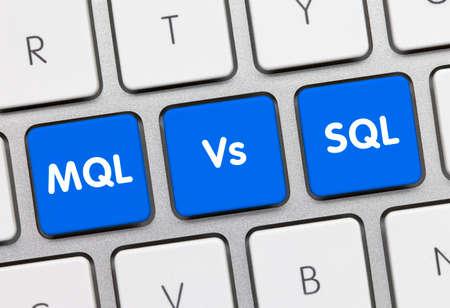 MQL Vs SQL Written on Blue Key of Metallic Keyboard. Finger pressing key.