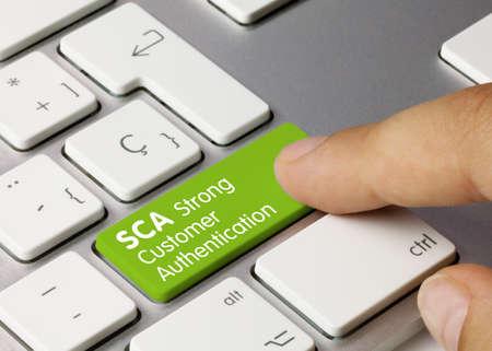 SCA Strong Customer Authentication Written on Green Key of Metallic Keyboard. Finger pressing key.