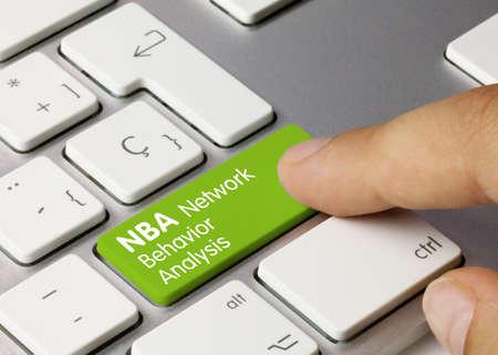 NBA Network Behavior Analysis Written on Green Key of Metallic Keyboard. Finger pressing key. Stock Photo