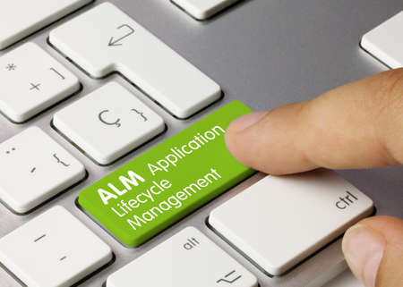 ALM Application Lifecycle Management Written on Green Key of Metallic Keyboard. Finger pressing key.