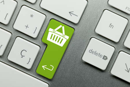 e-shop Written on Green Key of Metallic Keyboard. Finger pressing key. Stock Photo