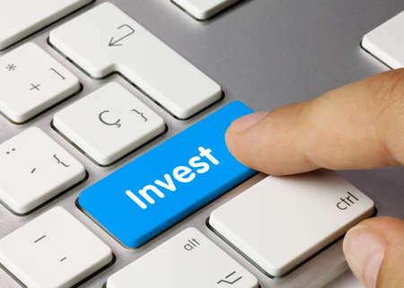 Invest Written on Blue Key of Metallic Keyboard. Finger pressing key.