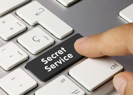 Secret Service Written on Black Key of Metallic Keyboard. Finger pressing key. 版權商用圖片