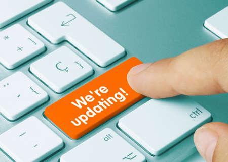 We're updating! Written on Orange Key of Metallic Keyboard. Finger pressing key.