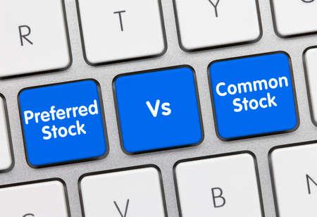 Preferred Stock Vs. Common Stock Written on Blue Key of Metallic Keyboard. Finger pressing key. Stock Photo