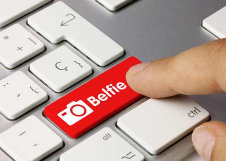 Belfie Written on Red Key of Metallic Keyboard. Finger pressing key.