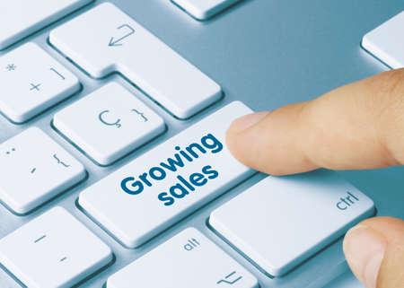 Growing sales Written on Blue Key of Metallic Keyboard. Finger pressing key. 免版税图像