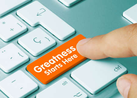Greatness Starts Here Written on Orange Key of Metallic Keyboard. Finger pressing key.