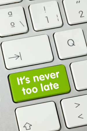 It's never too late Written on Green Key of Metallic Keyboard. Finger pressing key.