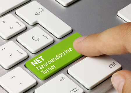 NET Neuroendocrine Tumor Written on Green Key of Metallic Keyboard. Finger pressing key.