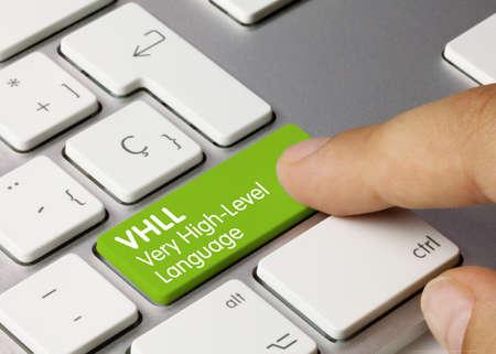 VHLL Very High-Level Language Written on Green Key of Metallic Keyboard. Finger pressing key.