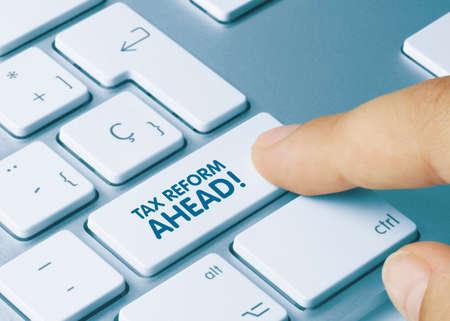 TAX REFORM AHEAD! Written on Blue Key of Metallic Keyboard. Finger pressing key.