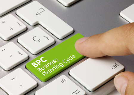 BPC - Business Planning Cycle Written on Green Key of Metallic Keyboard. Finger pressing key. Imagens