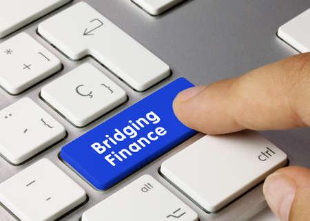 Bridging Finance Written on Blue Key of Metallic Keyboard. Finger pressing key. Banco de Imagens