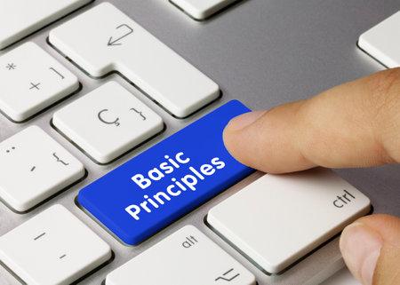 Basic principles Written on Blue Key of Metallic Keyboard. Finger pressing key. Zdjęcie Seryjne