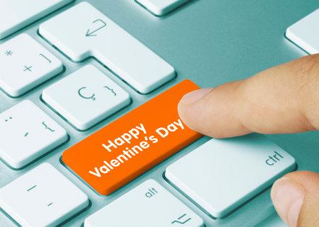 Happy Valentine's Day Written on Orange Key of Metallic Keyboard. Finger pressing key. Stock Photo