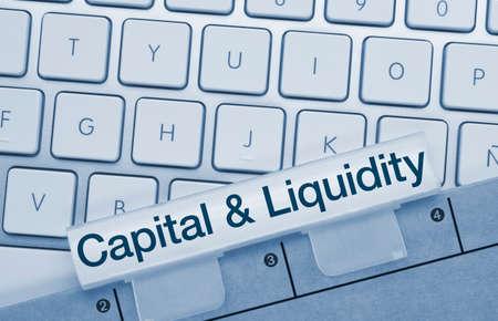 Capital & liquidity Written on Blue Key of Metallic Keyboard. Finger pressing key. Stok Fotoğraf