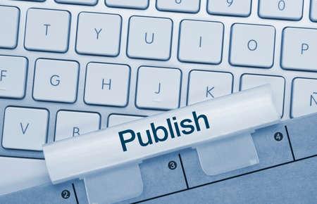 Publish Written on Blue Key of Metallic Keyboard. Finger pressing key.