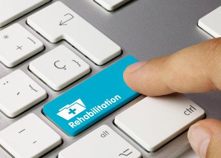 Rehabilitation Written on Blue Key of Metallic Keyboard. Finger pressing key.