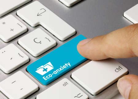 Eco-anxiety Written on Blue Key of Metallic Keyboard. Finger pressing key. Stok Fotoğraf