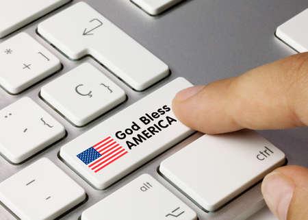 GOD BLESS AMERICA Written on White Key of Metallic Keyboard. Finger pressing key. Stok Fotoğraf