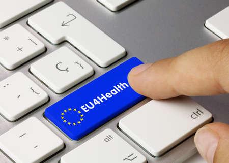 EU4Health Written on Blue Key of Metallic Keyboard. Finger pressing key.