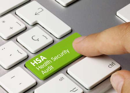 HSA Health Security Audit Written on Green Key of Metallic Keyboard. Finger pressing key.