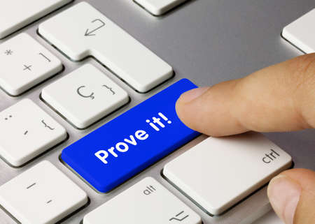 Prove it! Written on Blue Key of Metallic Keyboard. Finger pressing key.