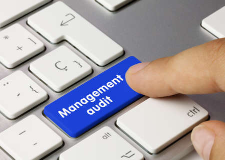 Management audit Written on Blue Key of Metallic Keyboard. Finger pressing key.