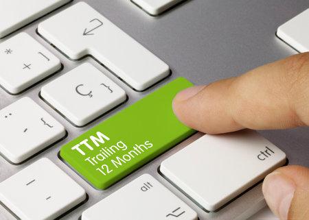 TTM Trailing 12 Months Written on Green Key of Metallic Keyboard. Finger pressing key. Stok Fotoğraf